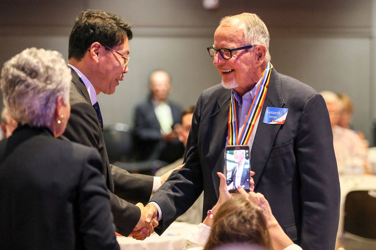 Kenneth Strum (right) shakes hands with Consul General Hyung-jong Lee after being presented his Ambassador for Peace Medal on Monday morning at Northwest Church in Lynnwood. (Kevin Clark / The Herald)