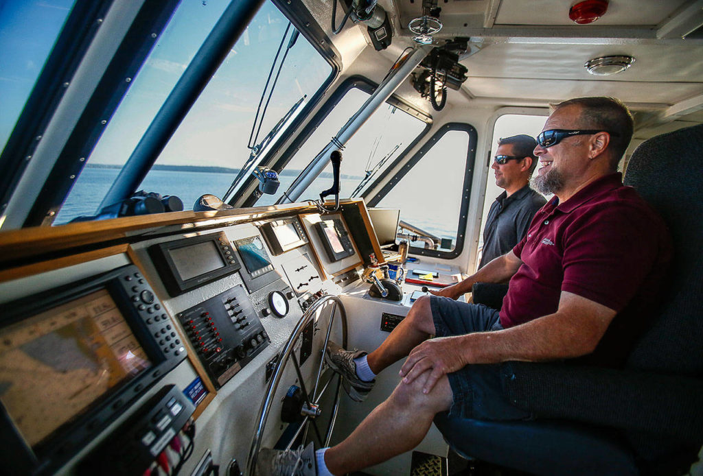 Captain Ray Brown (nearest) pilots the Hat Express early Thursday enroute to Hat Island as crew member Ryan Taisey, the first mate, watches for whales that have been spotted feeding nearby. (Dan Bates / The Herald)