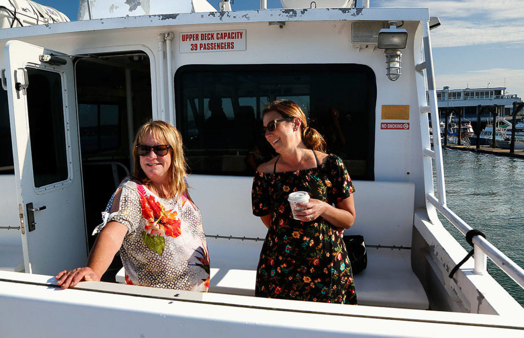 """Hat Island harbormaster Barb Conwell (left) and Michelle Brown, a """"snow bird"""" who splits her time between Hat Island and Arizona, share a laugh aboard the Hat Express, a private ferry that connects the island with Everett. Michelle's husband John Brown does maintenance on the island. (Dan Bates / Herald Photographer)"""