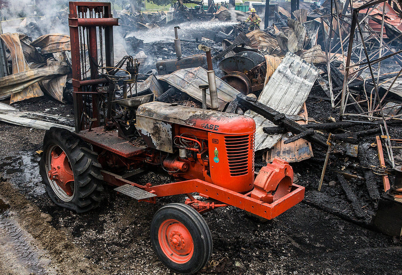A Monroe firefighter sprays water over the hotspots of the 100-year-old barn that caught fire at the Sky Valley Stock and Antique Tractor Show groundson Aug. 11 in Monroe.(Olivia Vanni / The Herald)