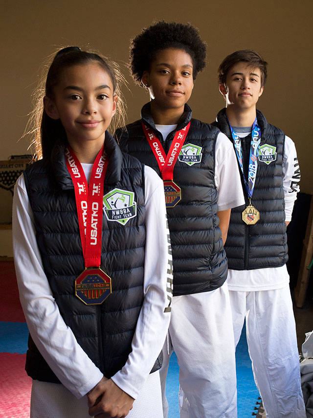 Northwest Black Belt Academy students Montana Miller, Akilah Franklin and Isaak Whitworth took gold medals in their recent national championship competitions. (Andy Bronson / The Herald)
