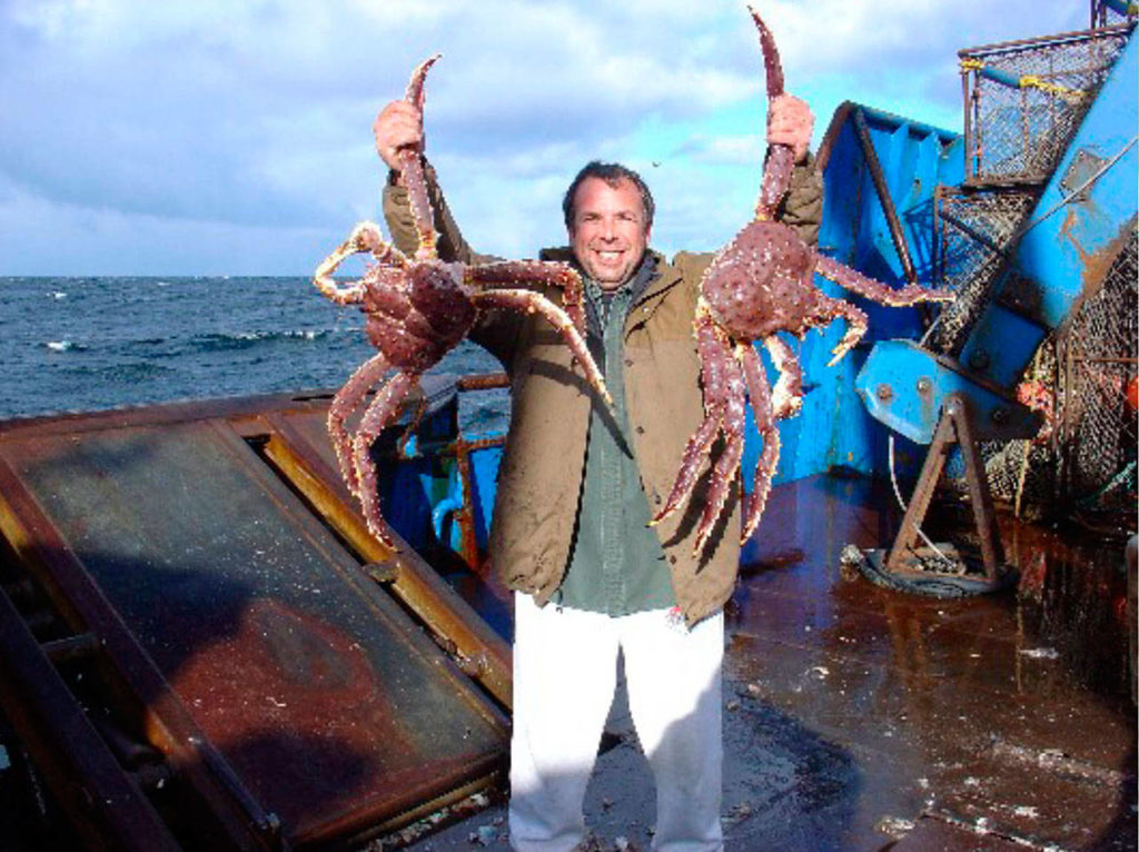 Dungeness Gear Works President Lance Nylander hoists two Alaskan blue king crabs on the deck of a ship.