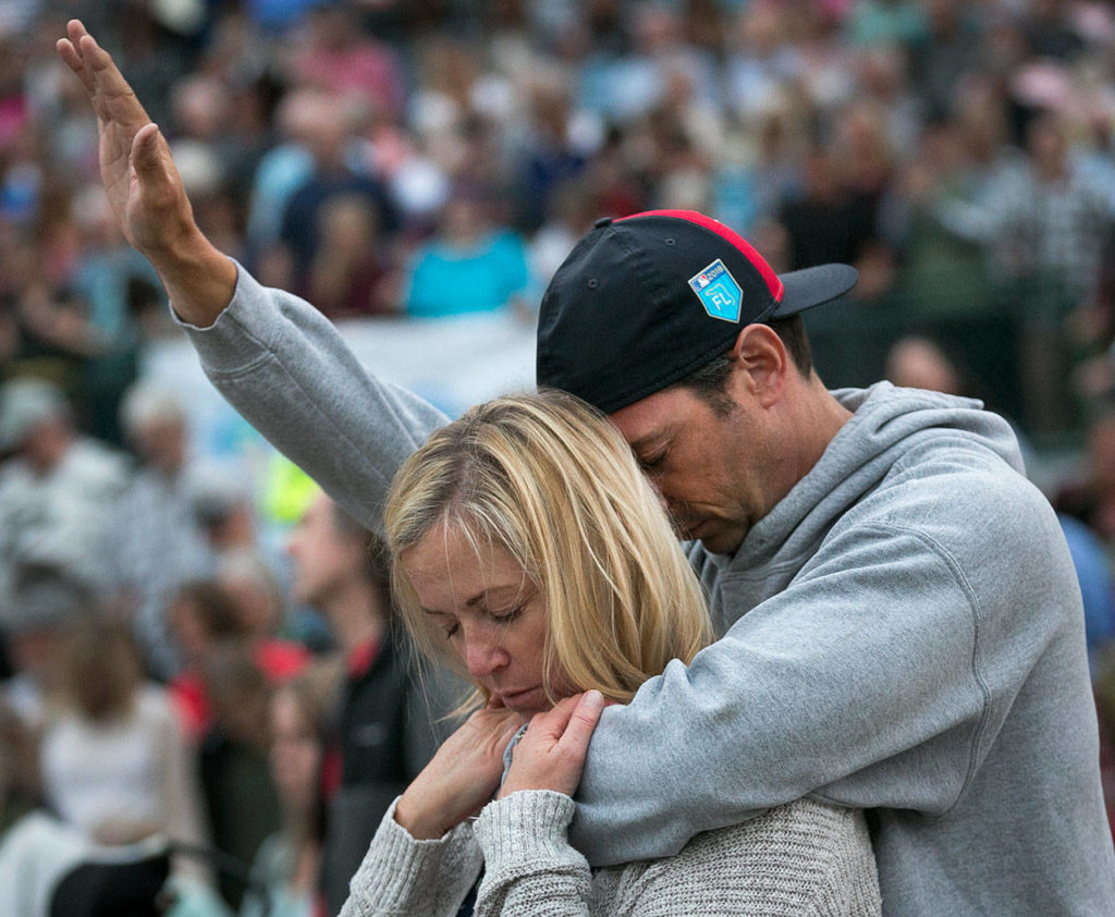Trina and Bobby Morrison pray during the Decision America Pacific Northwest Tour on Monday night at the Evergreen State Fairgrounds in Monroe. (Kevin Clark / The Herald)
