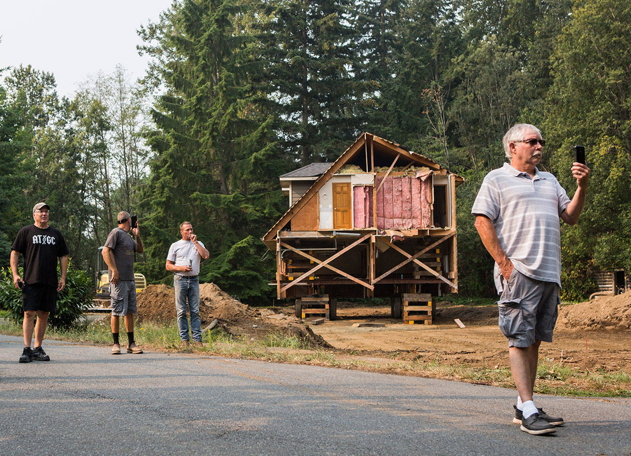 Local residents watch as a house is moved Wednesday down Bellflower Road in Bothell. (Olivia Vanni / The Herald)