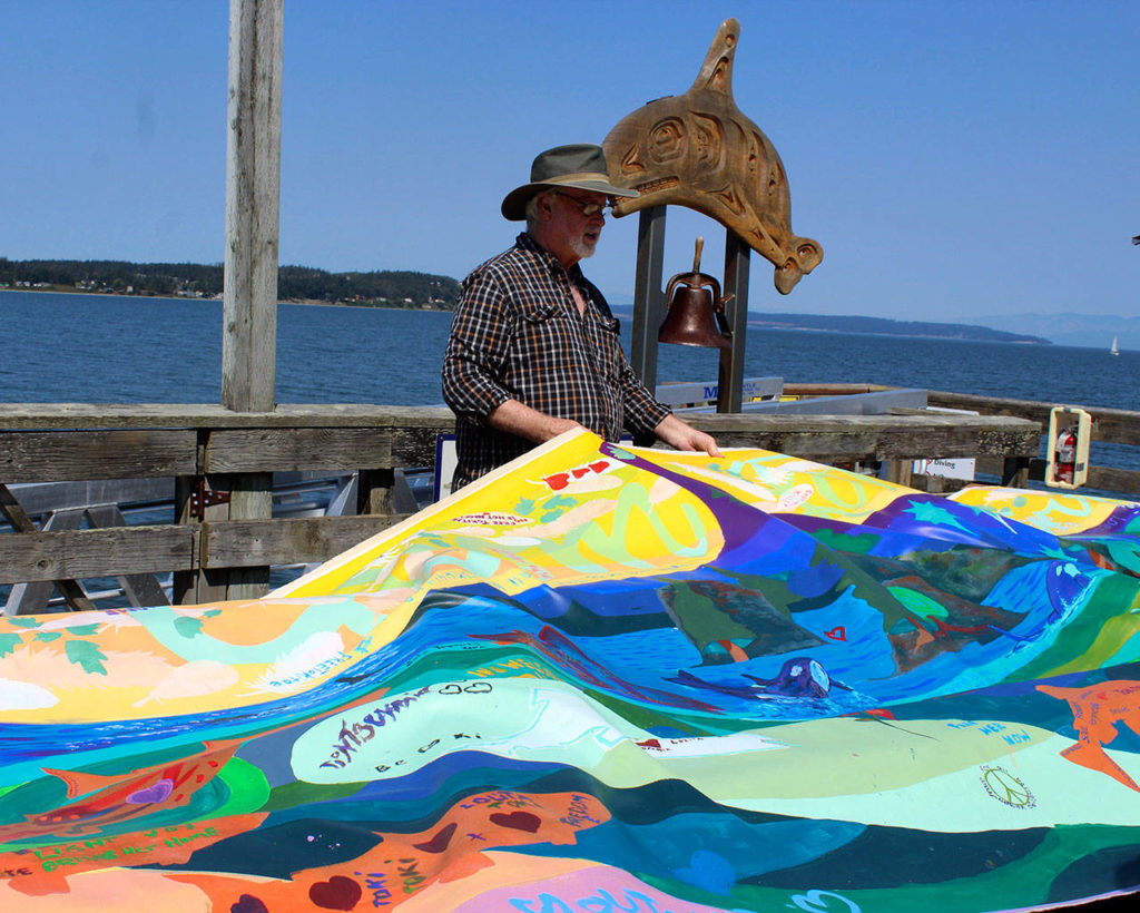 On the Coupeville wharf near the whale bell, Rick Baker helps unfurl a banner painted along the route of the Tokitae Totem Pole Journey undertaken by the Lummi Nation in May. (Patricia Guthrie/Whidbey News-Times)