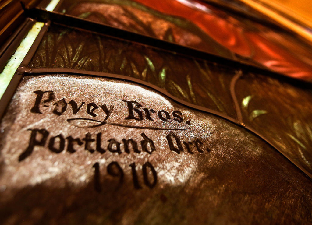 """In a corner of the large stained glass window facing east at the First Presbyterian Church in Everett is the Povey Bros., of Portland, Oregon, signature, dated 1910. The window depicts Christ teaching the """"Parable of the Lily."""" (Dan Bates / The Herald)"""