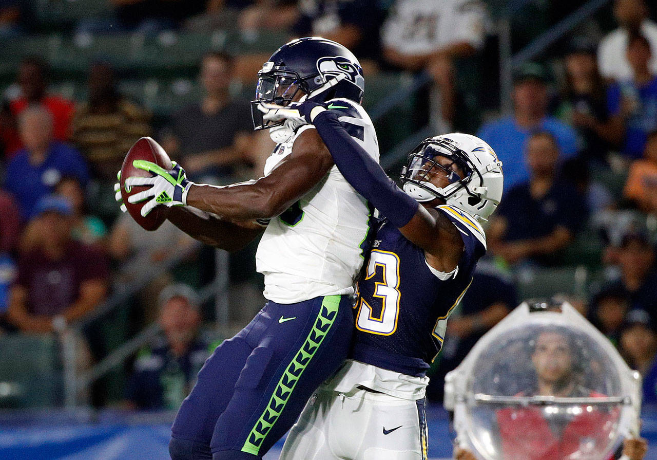 Seahawks wide receiver David Moore (left) makes a catch as Los Angeles Chargers cornerback Michael Davis defends during the first half of Saturday's preseason game in in Carson, California. (AP Photo/Jae C. Hong)