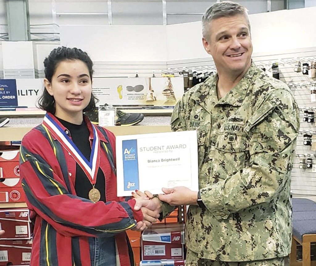 U.S. Navy Capt. Michael Davis, commanding officer of Naval Station Everett (right), congratulates Bianca Brightwell on receiving the Navy Exchange's A-OK Student Award. (Contributed photo)
