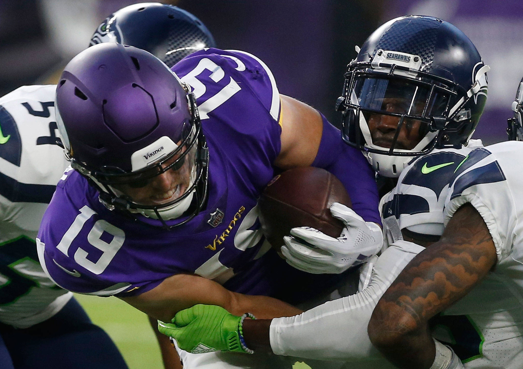 Vikings wide receiver Adam Thielen (19) is tackled by Seahawks cornerback Justin Coleman (right) after making a reception during the first half of a preseason game on Aug. 24, 2018, in Minneapolis. (AP Photo/Jim Mone)