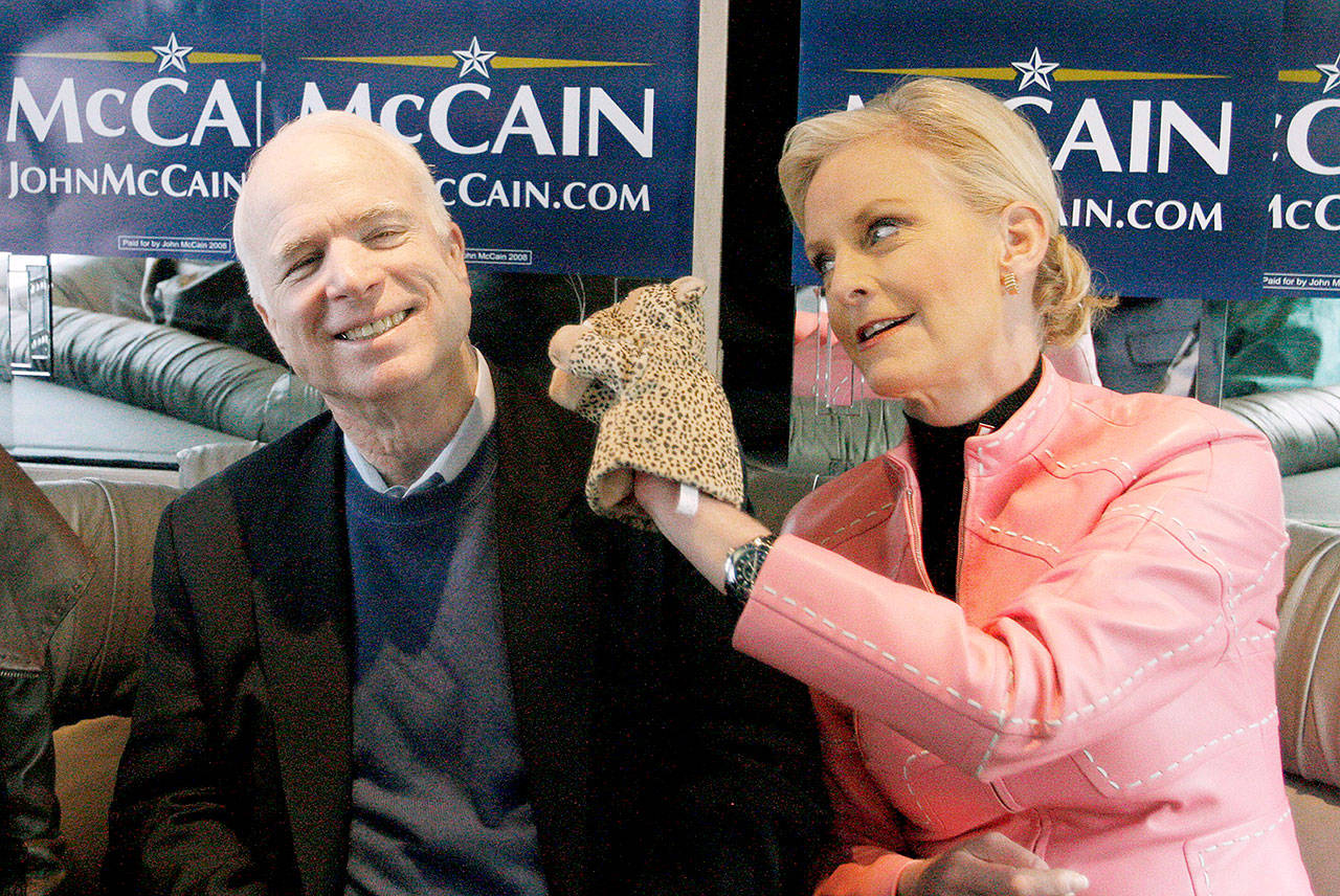 """Cindy McCain (left), wife of then-presidential hopeful Sen. John McCain, used a cheetah hand puppet to make her husband laugh in 2008 as they rode the """"Straight Talk Express"""" campaign bus. (AP Photo/Charles Dharapak, File)"""