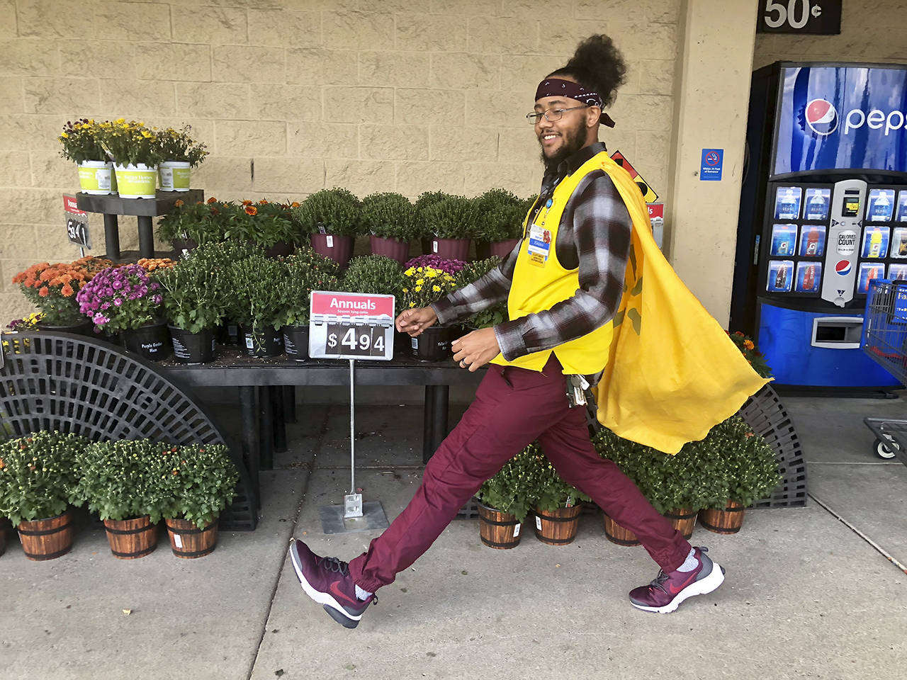 Isaiah Owens strolls past some plants at Walmart in his cape. Shoppers call him Captain Walmart, SuperWalmartman and other superhero names. (Andrea Brown / The Herald)