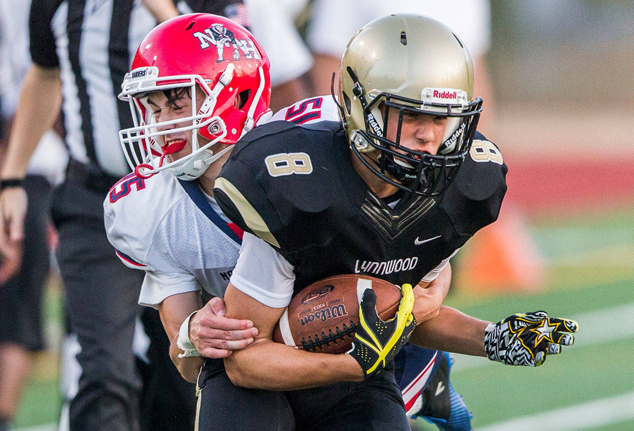 Lynnwood's Tanner Fahey is tackled by Nathan Hale's Chris Coon during Fridays game against Nathan Hale on Aug. 31, 2018 in Edmonds, Wa. (Olivia Vanni / The Herald)