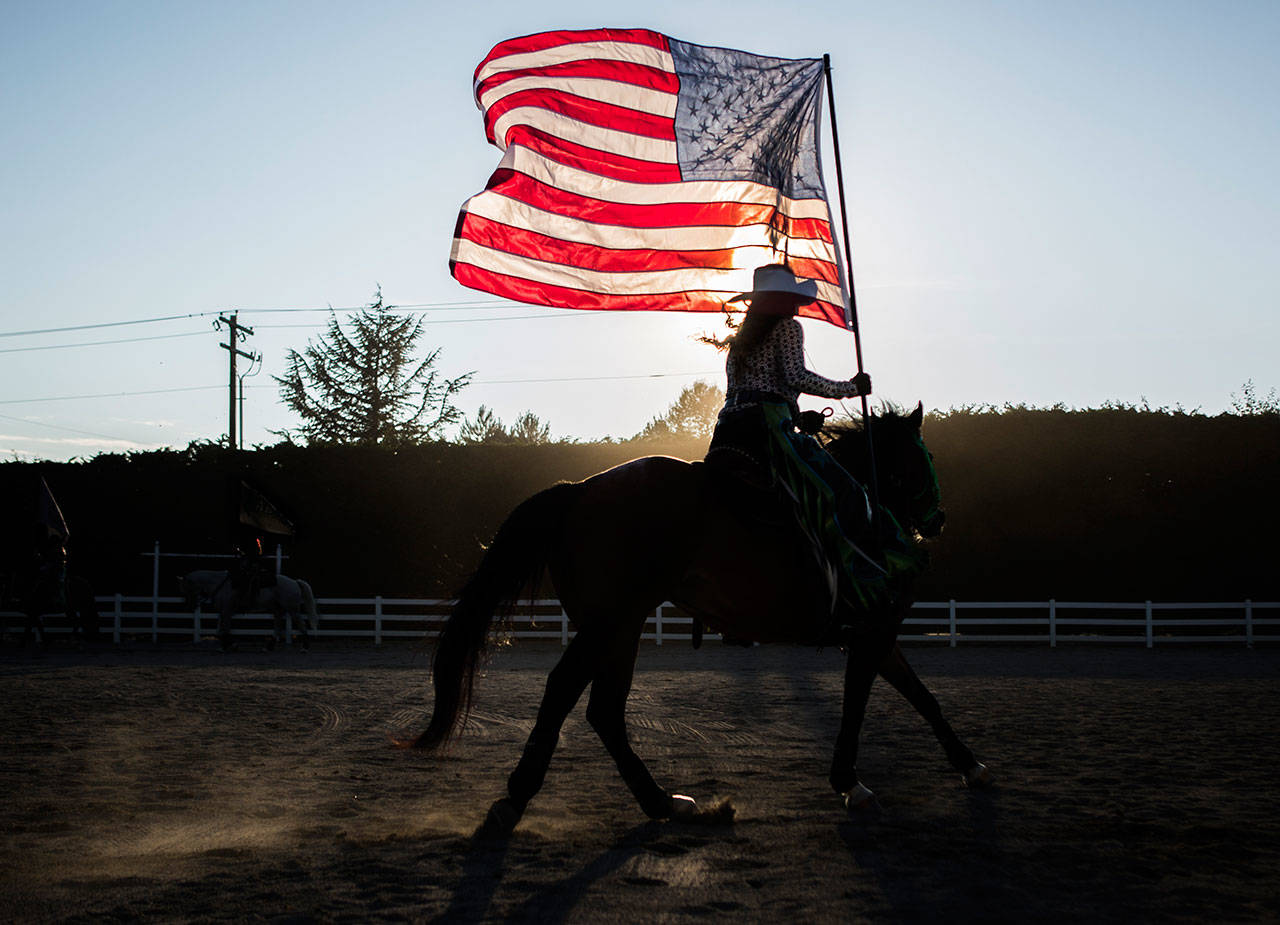 A member of the Stirrin' Dust Drill Team practices in the outdoor arena before the start of the Pro-West Rodeo at the Evergreen State Fair on Sept. 1, 2018 in Monroe, Wa. (Olivia Vanni / The Herald)