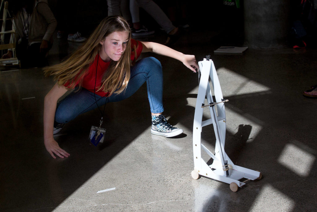 Fifth-grader Frankee Powers walks behind her team's gravity car as it moves down a hallway at the University of Washington on Wednesday, Sept. 12, 2018 in Seattle, Wa. Students from Marshall Elementary in Marysville built gravity cars as part of a one week engineering program. (Andy Bronson / The Herald)
