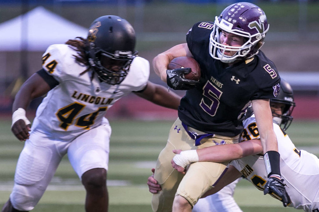 Lake Stevens' Tom Lewis is tackled by Lincoln's Troy Atkin with Lincoln's Janoah Thomas (left) closing during a game on Sept. 7, 2018, at Lake Stevens High School. Lake Stevens won 38-21. (Kevin Clark / The Herald)