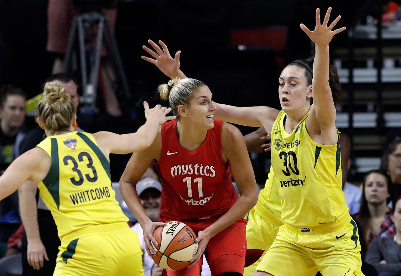 Washington's Elena Delle Donne (11) looks for room to pass as Seattle's Sami Whitcomb (33) and Breanna Stewart defend in the first half of Game 2 of the WNBA finals Sunday in Seattle. (AP Photo/Elaine Thompson)