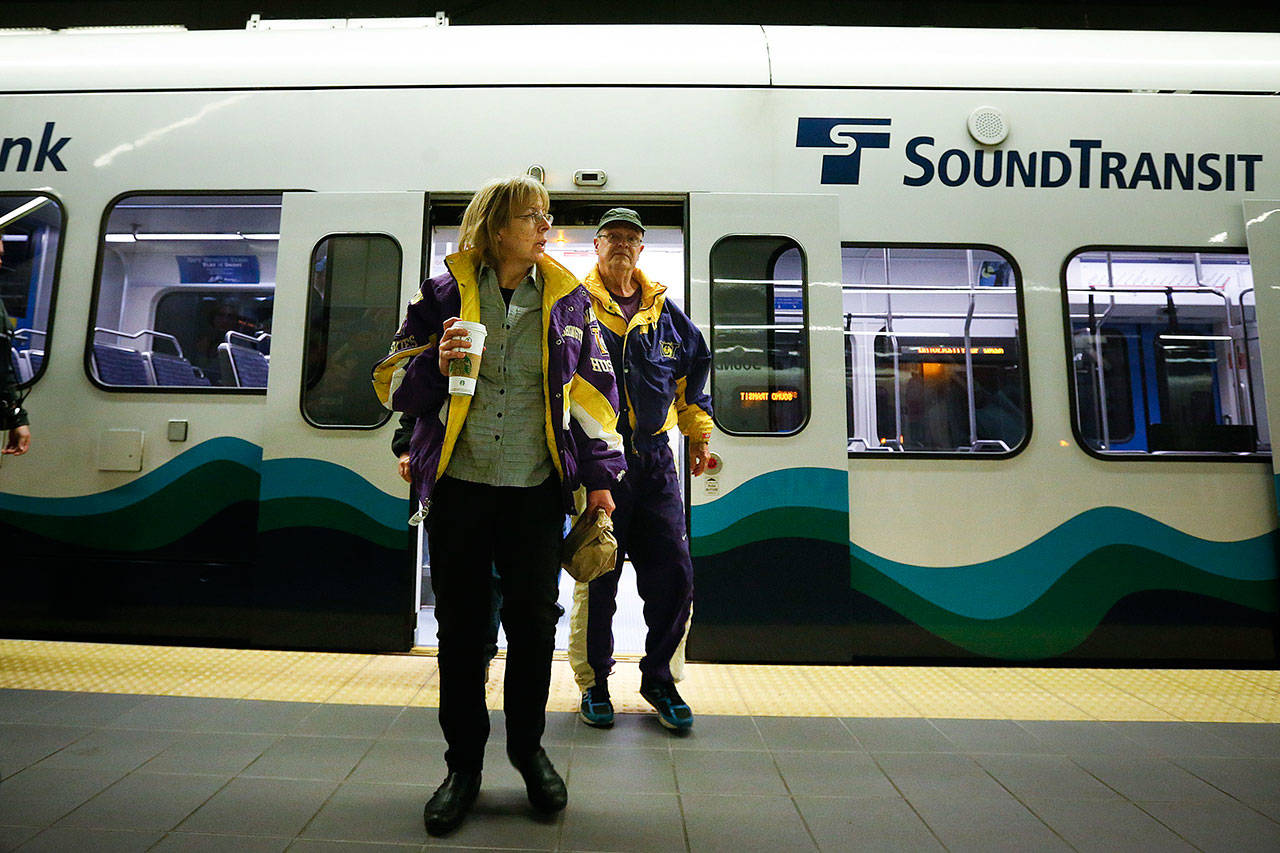 Anne and Jon Nelson of Seattle exit a light-rail train at University of Washington Station in Seattle in April 2016. (Ian Terry / Herald file photo)