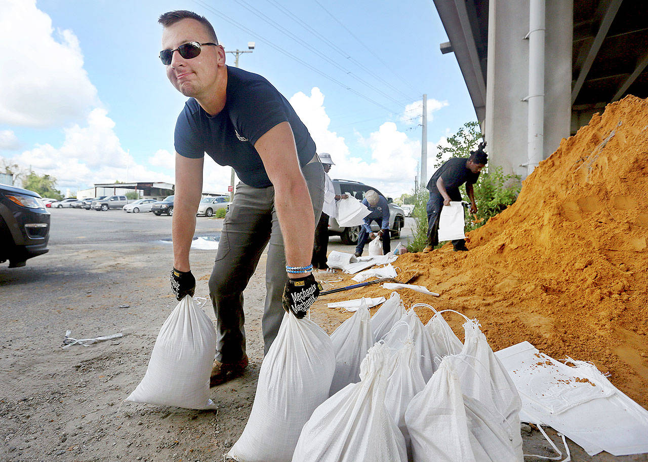 Kevin Orth loads sandbags into cars to prepare for Hurricane Florence on Monday in Charleston, South Carolina. (Grace Beahm Alford/The Post And Courier via AP)