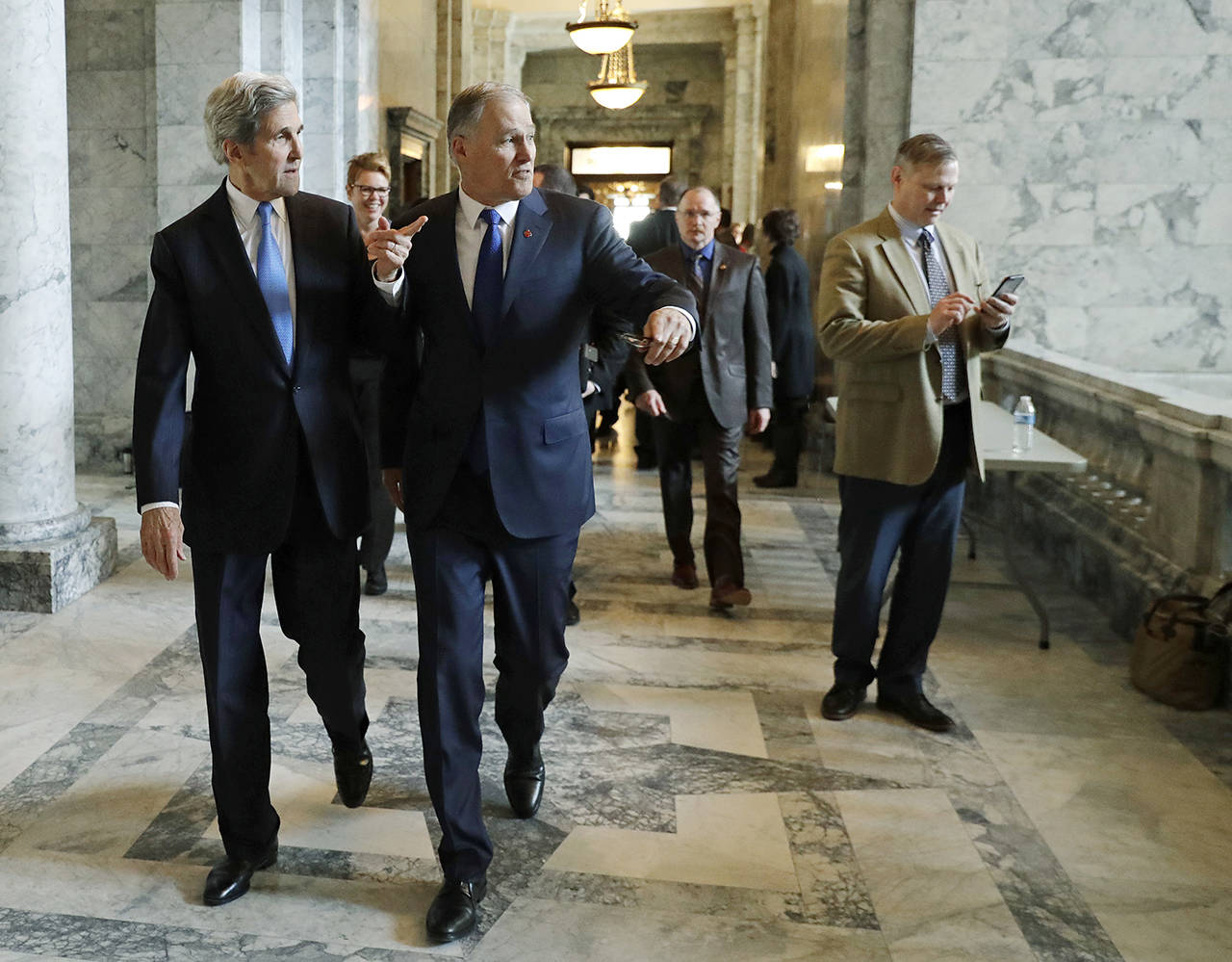 Former U.S. Secretary of State John Kerry (left) walks with Gov. Jay Inslee (center) on Feb. 13, 2018, during a visit hosted by Inslee to participate in meetings discussing the governor's proposed tax on fossil fuel emissions. (AP Photo/Ted S. Warren, file)