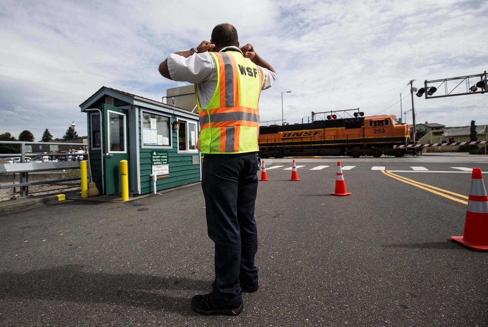 Washington State Ferries traffic attendant Brian Green plug his ears as a train blows its horn while heading south at the Edmonds Ferry dock on Friday, Sept. 21, 2018 in Edmonds, Wa. While Amtrak and the Sounder keep to a fixed schedule, the BNSF trains randomly block traffic when heading north or south. (Andy Bronson / The Herald)