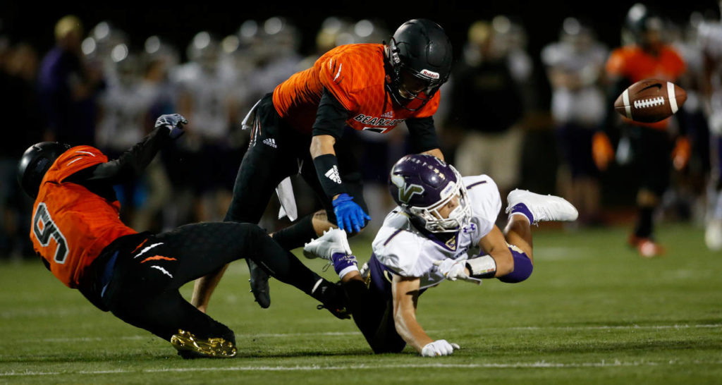 Two Monroe players break up a pass intended for Lake Stevens' Ian Hanson during Friday night's game in Monroe. (Andy Bronson / The Herald)