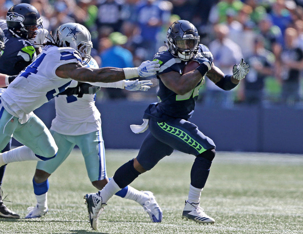 Seahawks' Chris Carson escapes a tackle during the game against the Dallas Cowboys on Sunday in Seattle. Carson rushed for a career-high 102 yards in the game. (Olivia Vanni / The Herald)