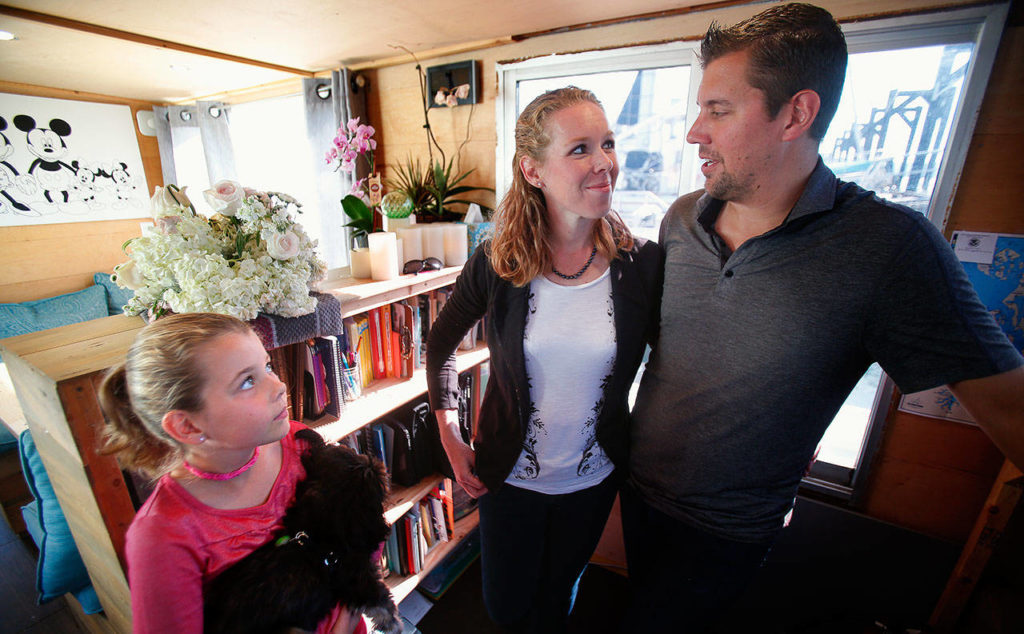 In the family's school, next to the general living, eating and playing area, the Taiseys have a nice library with good light. Arianna, 10, listens while Ryan and Jacy talk about homeschooling and their faith. (Dan Bates / The Herald)