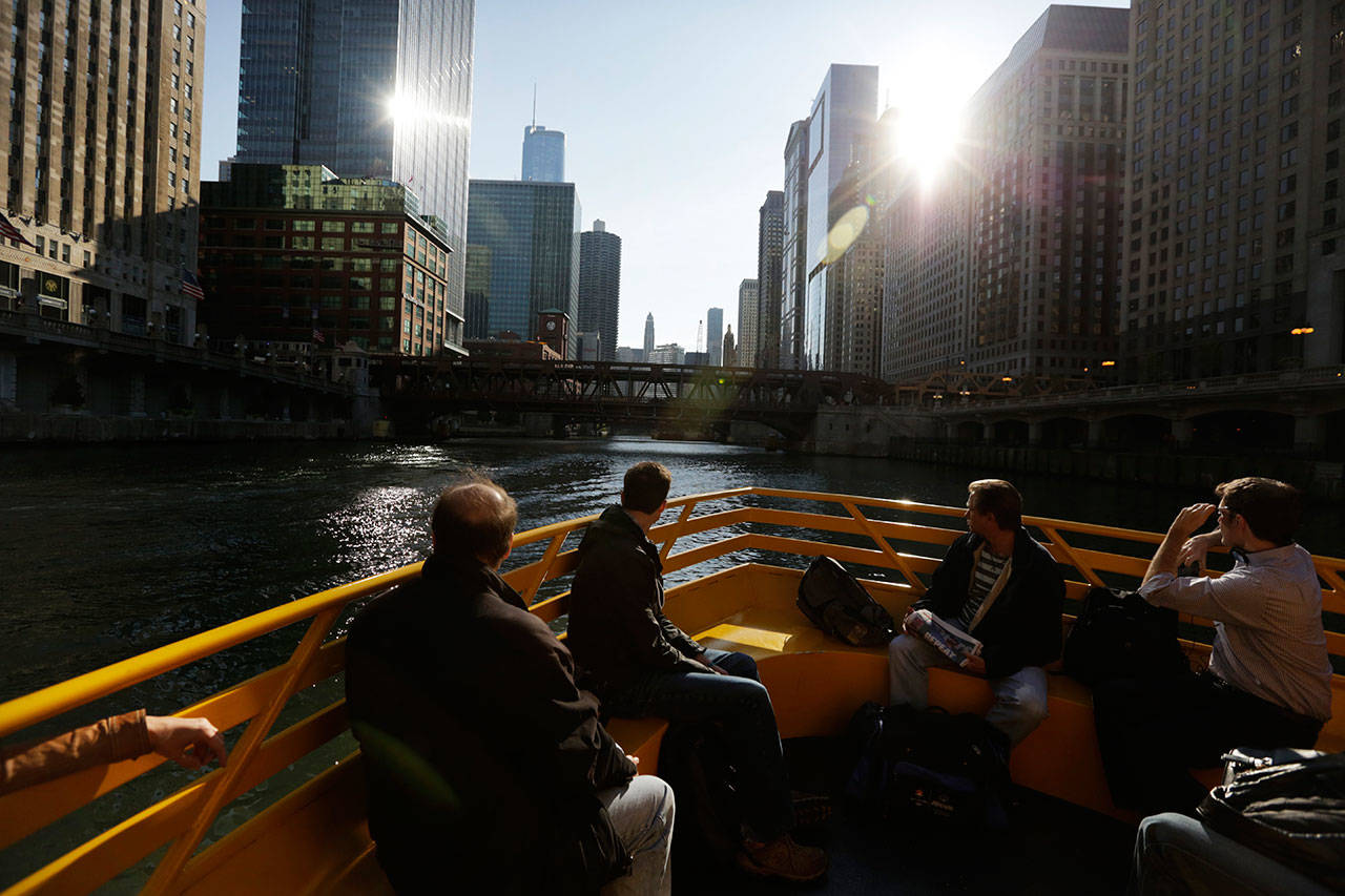 Morning commuters ride a water taxi up the Chicago River to Michigan Avenue in Chicago. No matter your age, what the Federal Reserve does to interest rates will most likely affect you. (M. Spencer Green / AP file)