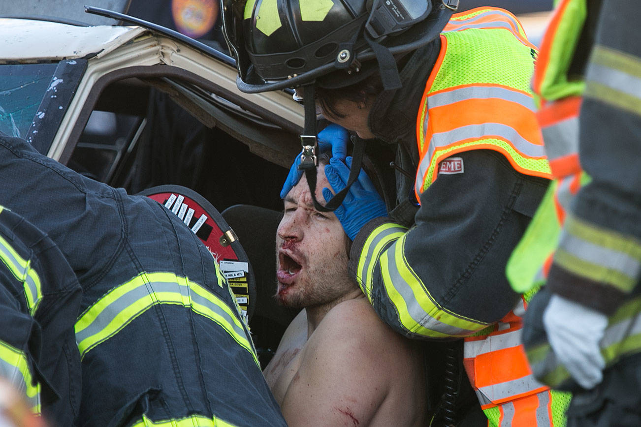 First responders work to free a driver of a two-car accident on the 7100 block of Evergreen Way Wednesday afternoon in Everett on September 26, 2018 (Kevin Clark / The Herald)