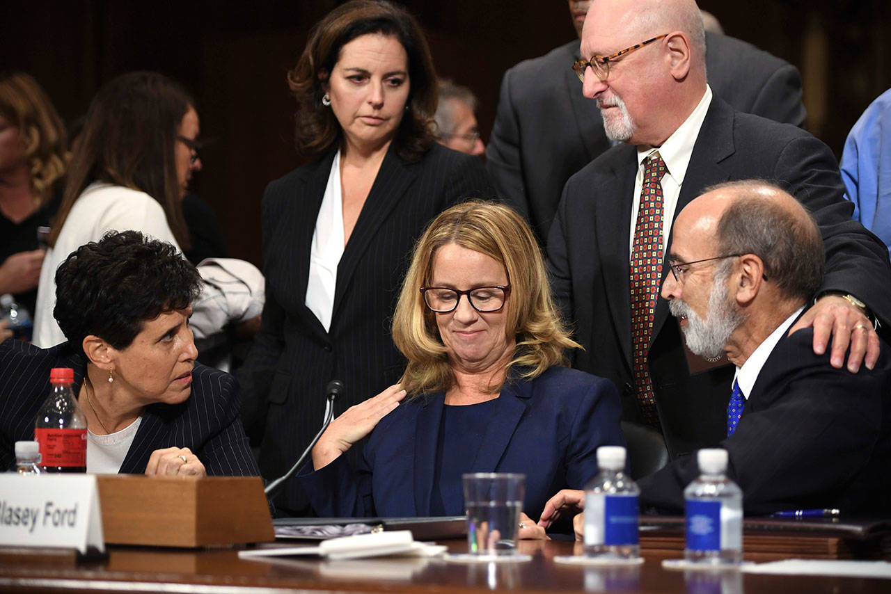 Christine Blasey Ford takes a break in her testimony before the Senate Judiciary Committee on Thursday on Capitol Hill in Washington. Lawyers seated are Debra Katz and Michael Bromwich. (Saul Loeb/ Pool Image via AP)