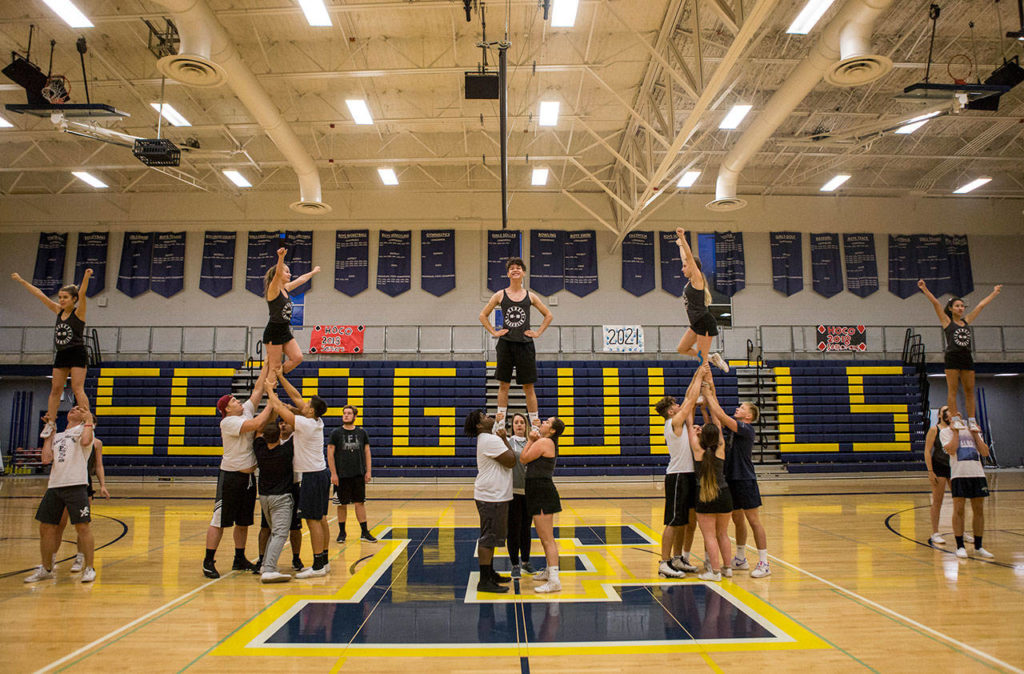 Everett High School cheerleaders and football players run through their full routine during rehearsal in the Everett High School gym on Sept. 26. (Olivia Vanni / The Herald)