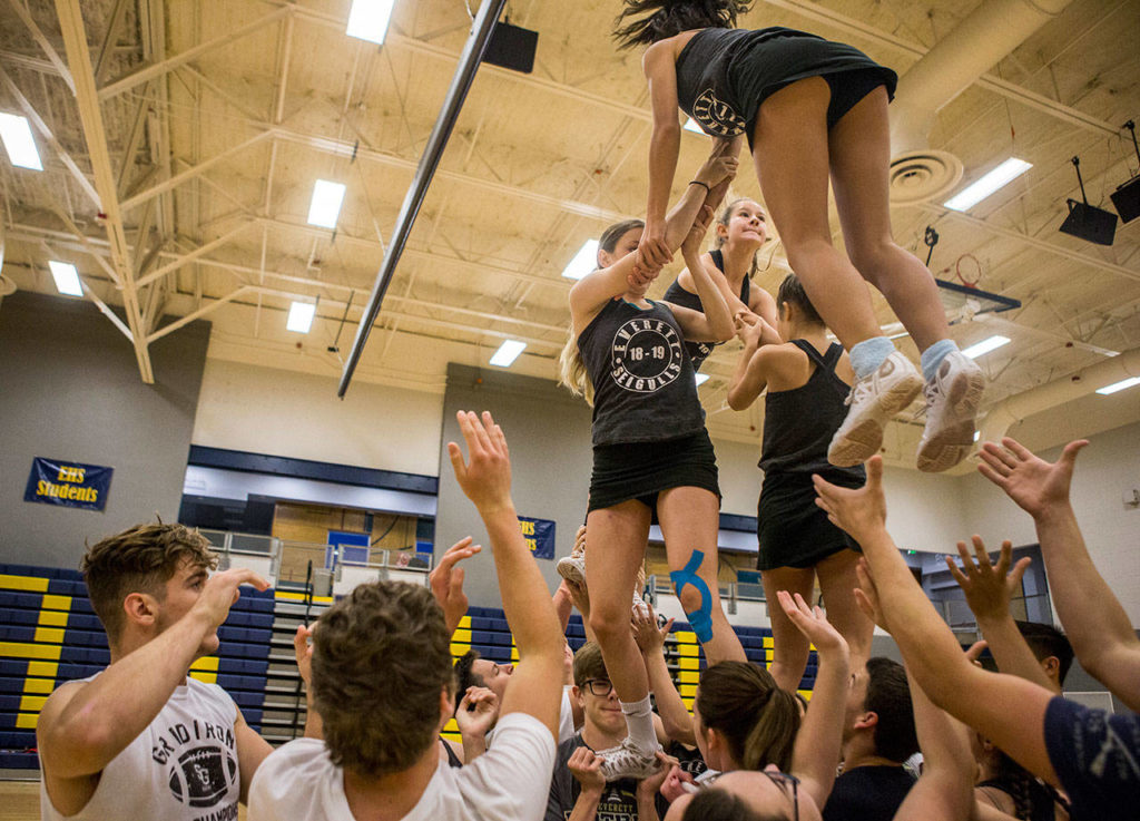 Everett High School cheerleaders and football players work together during rehearsal in the Everett High School gym on Sept. 26. (Olivia Vanni / The Herald)