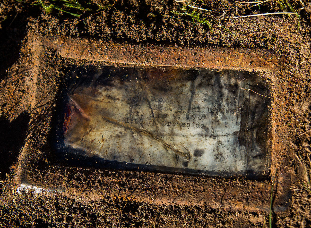 A grave tag labeled John Doe marks the plot at Cypress Lawn cemetery being exhumed on Oct. 17 in Everett. (Olivia Vanni / The Herald)