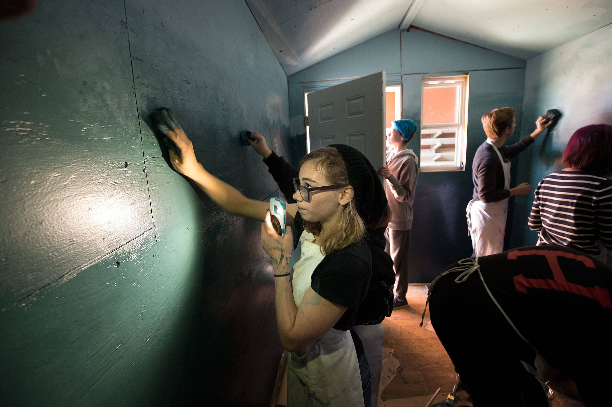 Snohomish High School student Hailey Knie uses her cellphone Monday to light up the wall where she is blending colors of paint in a tiny home at the school. The home was built by classmates and painted by students from the Art Honor Society, and will be used to house the homeless in Seattle. (Andy Bronson / The Herald)