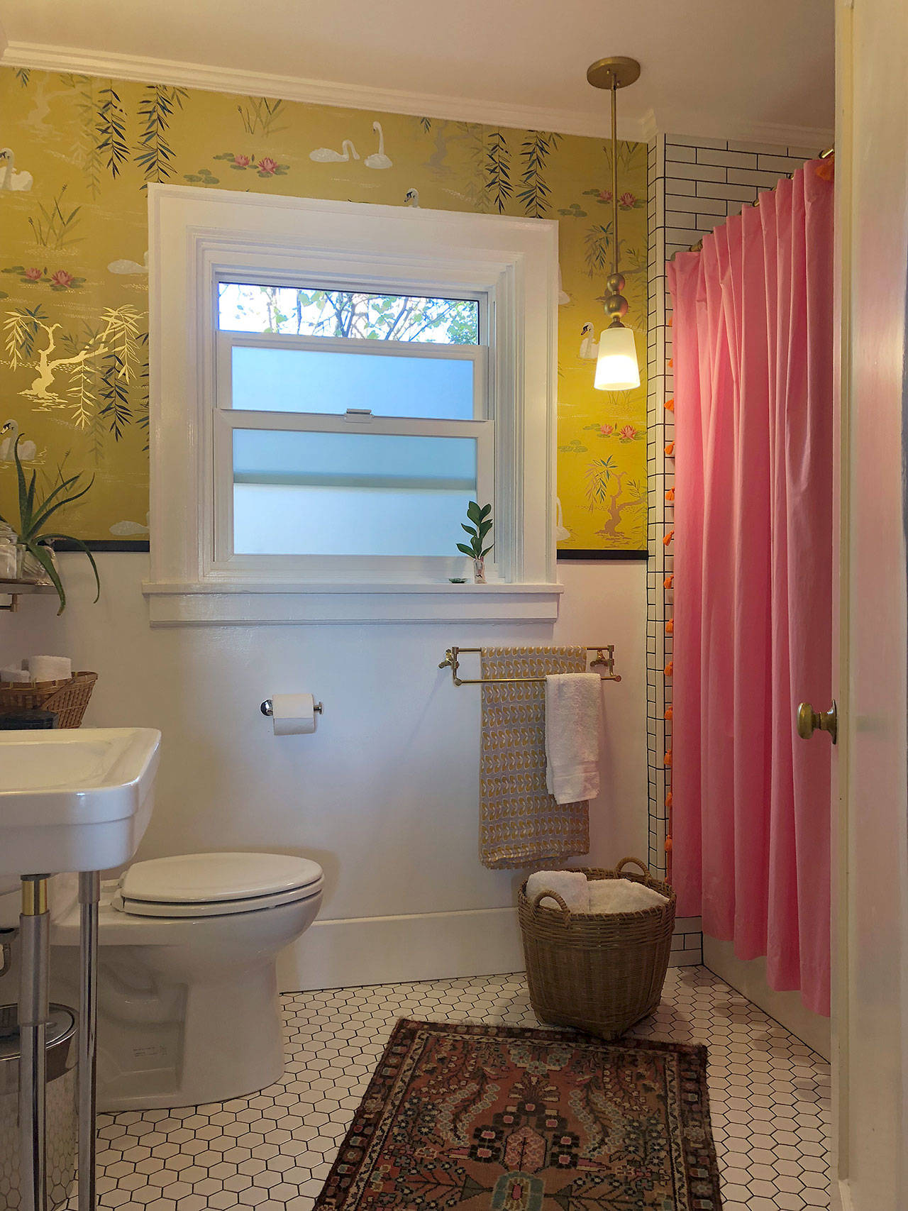 Bright colors from the wallpaper and shower curtain help add life to the more staid tile and fixtures in the remodeled bathroom. (Aaron Swaney)