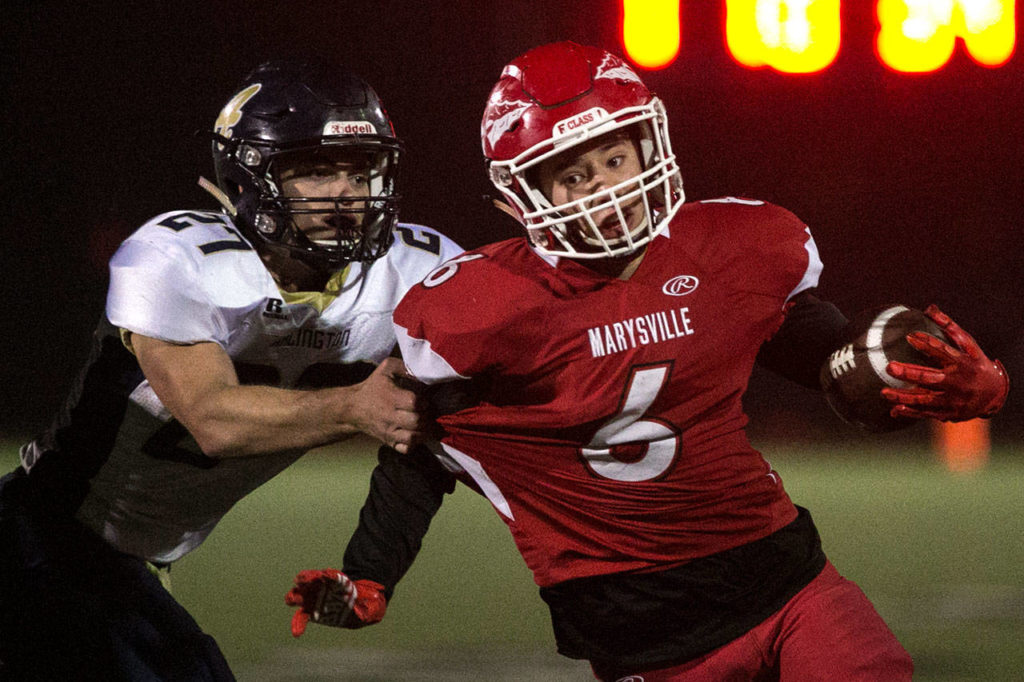Marysville Pilchuck's Dillon Kuk (right) carries the ball with Arlington's Kristain Fairbanks attempting a tackle during a game on Oct. 19, 2018, at Quil Ceda Stadium in Marysville. (Kevin Clark / The Herald)