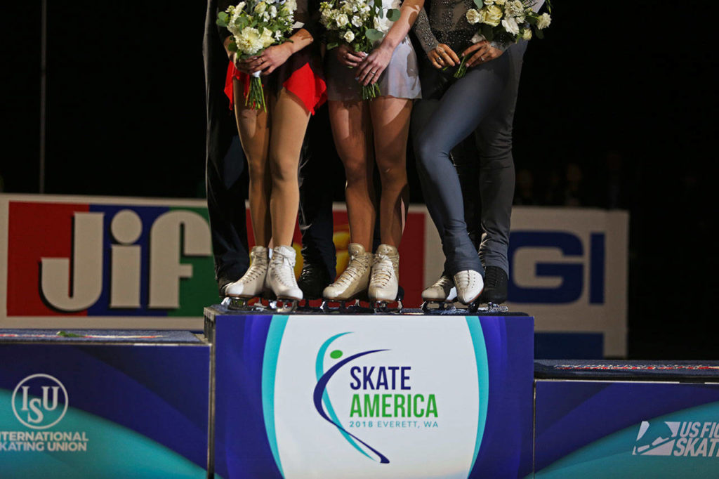 Pairs free skating winners stand on the podium for photos during the medal ceremony at the 2018 Skate America competition on Saturday at Angel of the Winds Arena in Everett. (Olivia Vanni / The Herald)