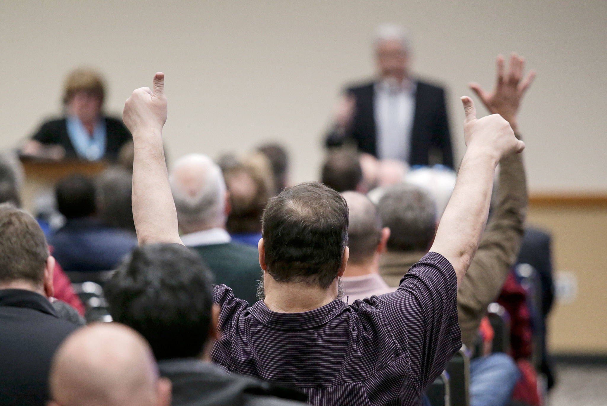 A speaker gets thumbs up during a Federal Aviation Administration hearing at the Lynnwood Convention Center on Monday about passenger service at Paine Field. (Andy Bronson / The Herald)