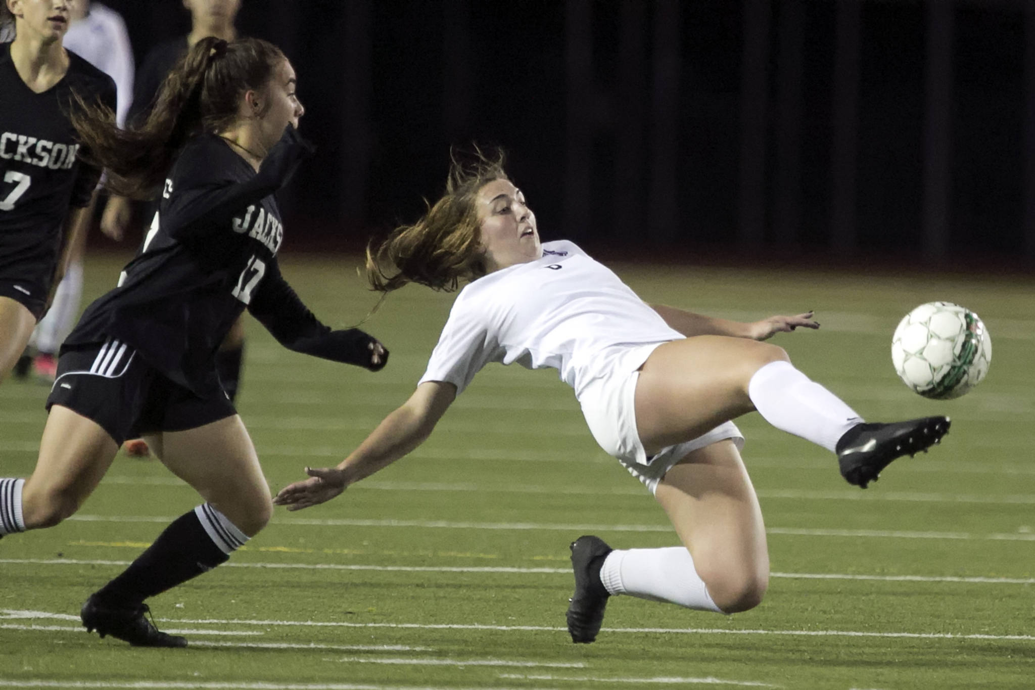 Lake Stevens' Samantha Foley (right) attempts a clearing kick with Jackson's Natalie Hawkins (left) trailing at Everett Memorial Stadium on Oct. 25. (Kevin Clark / The Herald)