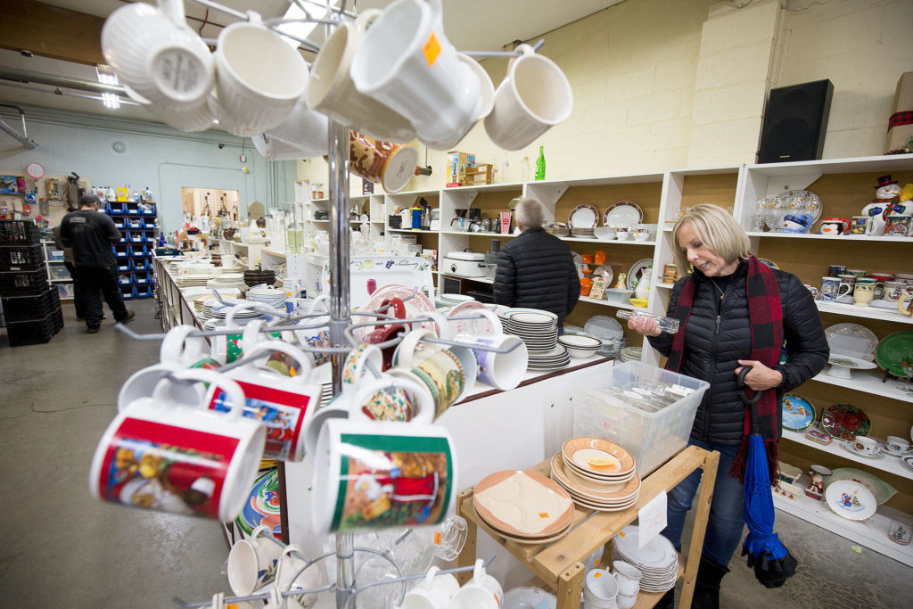 Nancy Hills, of Bonney Lake, looks over bottles at the Good Cheer Thrift Store on Nov. 9 in Langley. There are two on the island that fund 80 percent of the revenue for the food bank. The store in downtown Langley is a popular stop for tourists and islanders. (Andy Bronson / The Herald)