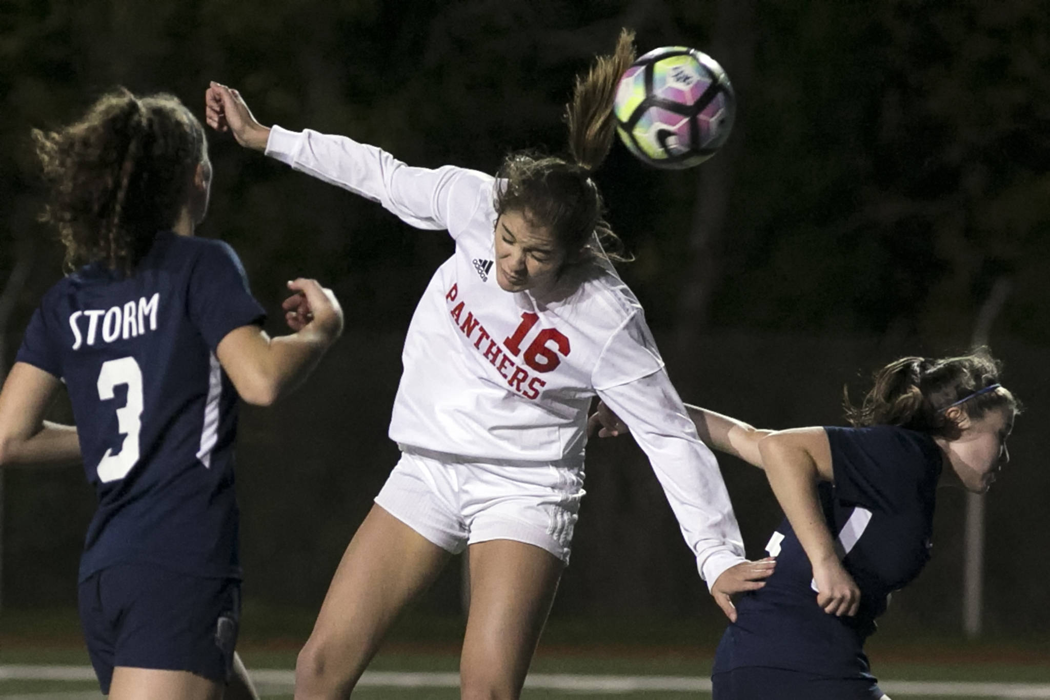 Snohomish's Taylor Khorrami makes a header for a goal with Squalicum's Audra Johnson (left) and Jamie Dierdorf defending during the NW District 1 3A Soccer Tournament at Shoreline Stadium on Oct. 30. (Kevin Clark / The Herald)