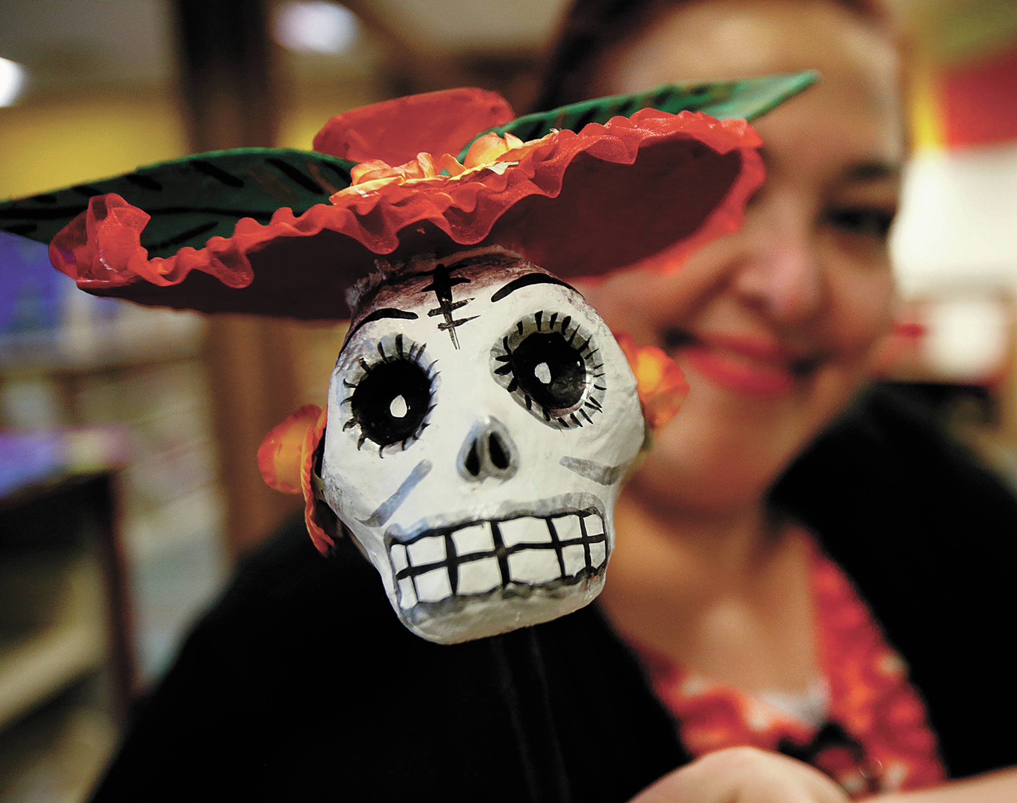 Helping set up a Dia de los Muertos display in the Lynnwood Library was Lupita Zamora, who holds up a skeleton head on a stick. (Dan Bates / The Herald)
