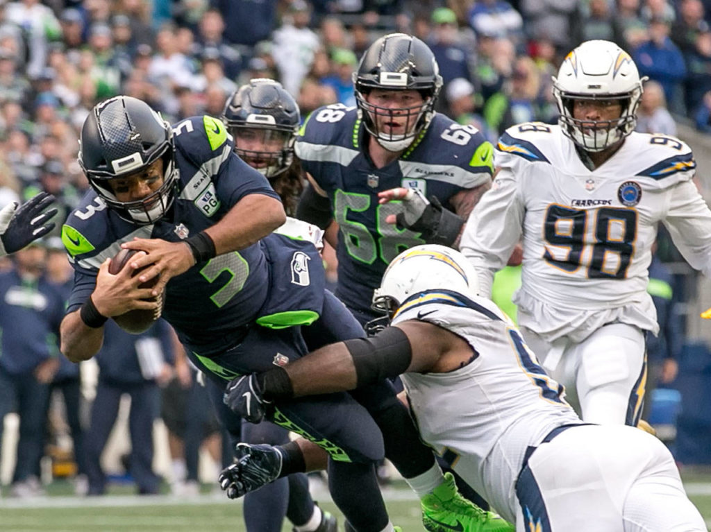 Seahawks quarterback Russell Wilson is tackled by Chargers defensive lineman Brandon Mebane Sunday afternoon at CenturyLink Field in Seattle on November 4, 2018. Chargers won 25-17. (Kevin Clark / The Herald)