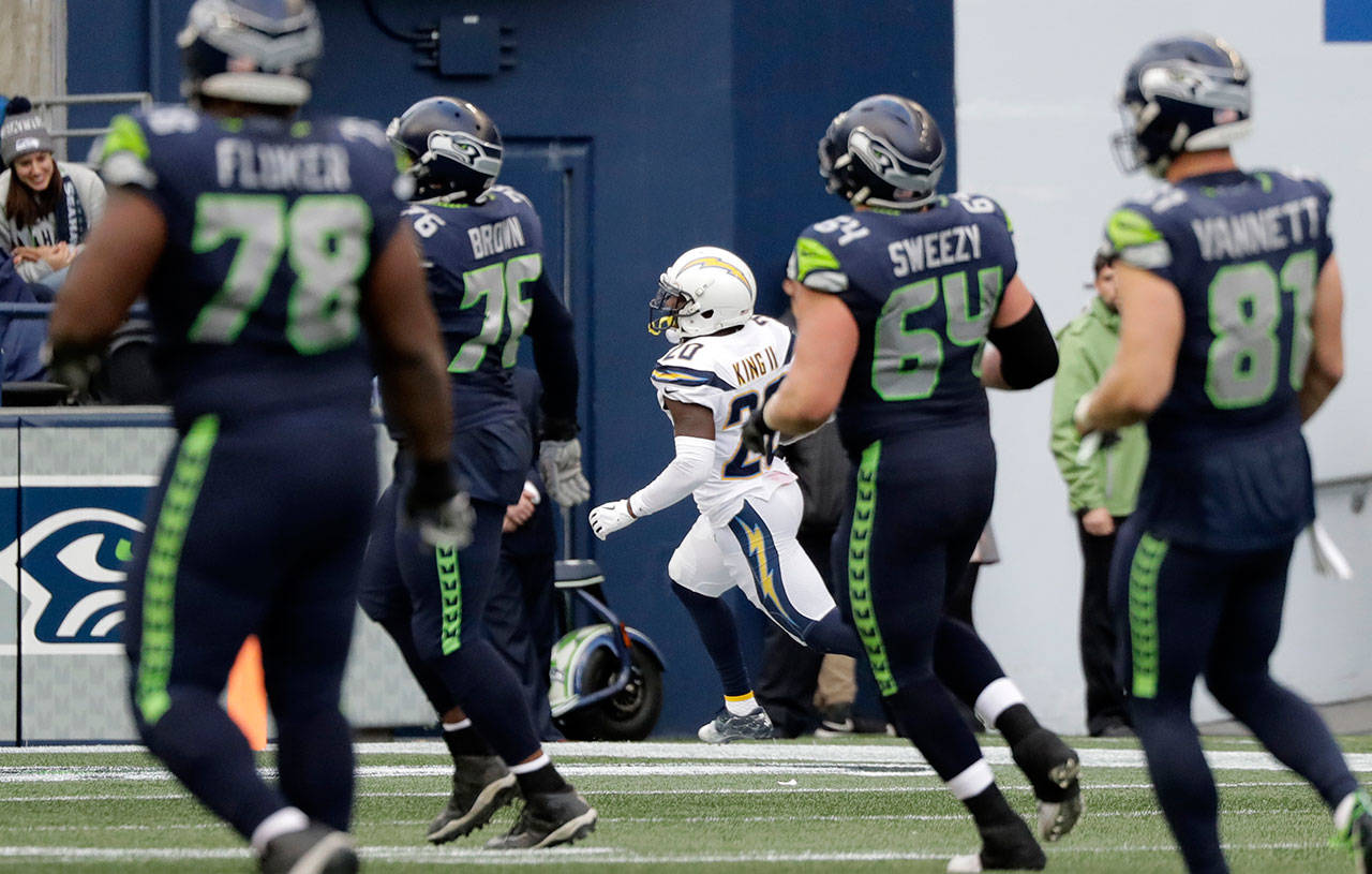 Seahawks players watch from a distance as Chargers defensive back Desmond King II returns a fourth-quarter interception for a touchdown Sunday at CenturyLink Field. (AP Photo/Ted S. Warren)