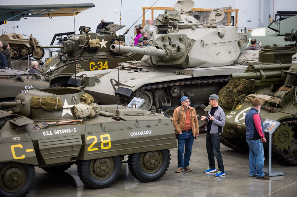 Visitors talk between a half-dozen tanks in the new hangar at the Flying Heritage & Combat Armor Museum at Paine Field on Saturday, Nov. 10, 2018 in Everett. (Andy Bronson / The Herald)