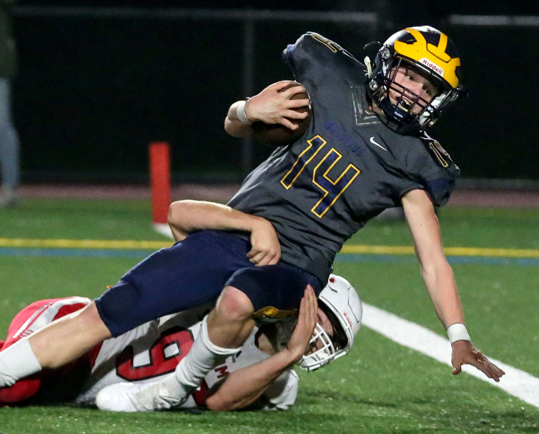 Bellevue's Alex Reid falls across the goal line for a touchdown over Snohomish's Noah Dunham on Friday in Bellevue. (Kevin Clark / The Herald)