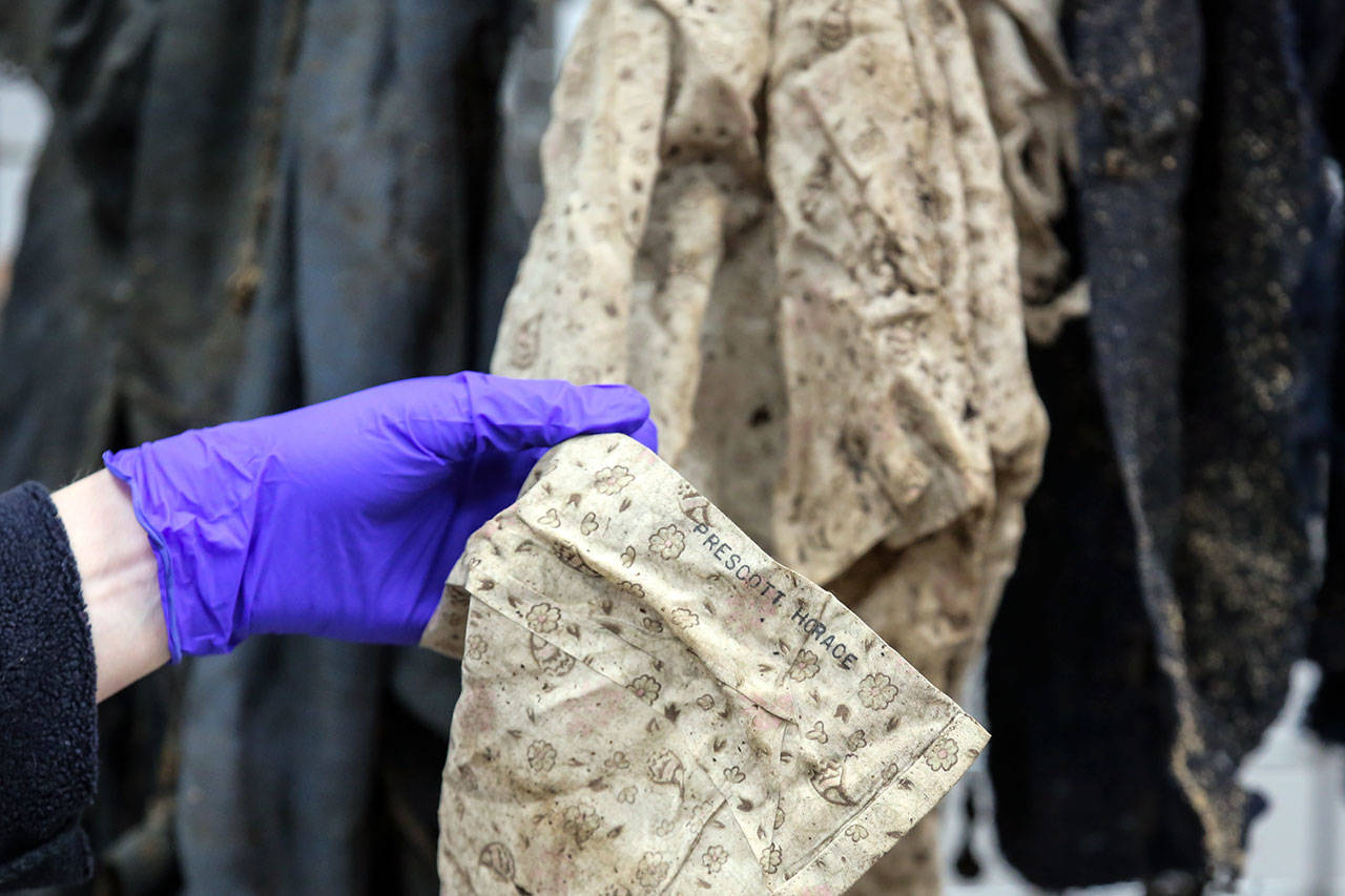 A name stenciled on the inside of a shirt may help to solve a 40-year-old cold case from the Lynnwood area. Bones that were found near the shirt were examined Nov. 13 at the Snohomish County Medical Examiner. (Kevin Clark / The Herald)