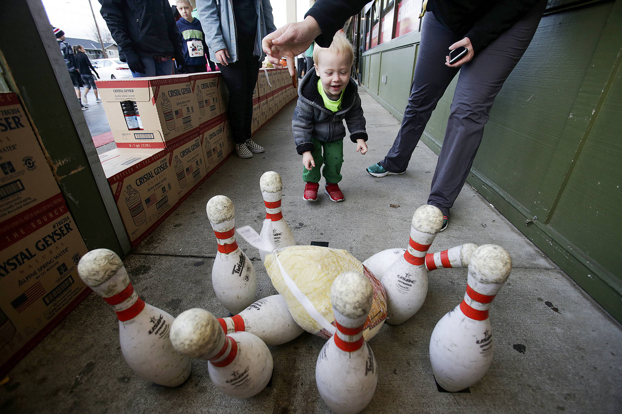 "Liam Mourning, 6, gets a hand at Turkey bowling from his mother Shelly outside Grocery Outlet at the <a href=""https://www.heraldnet.com/news/hundreds-run-through-arlington-before-thanksgiving-dinner/"" target=""_blank"">Turkey Trot 5K</a> on Nov. 22 in Arlington. (Andy Bronson / The Herald)"