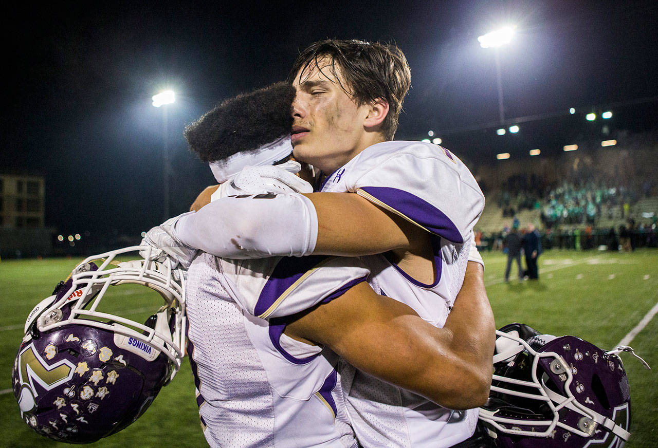 Lake Stevens' Ian Hanson (right) hugs Isaiah Harris after beating Woodinville in a 4A state state semifinal game on Nov. 24, 2018, at Pop Keeney Stadium in Bothell. (Olivia Vanni / The Herald)