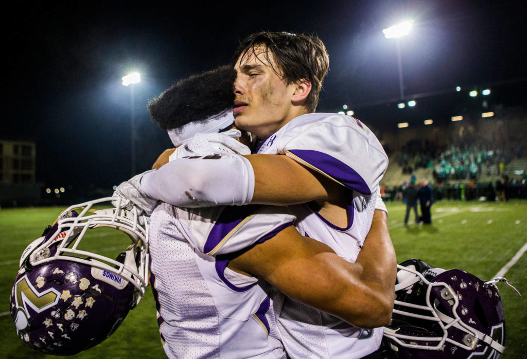 Lake Stevens' Ian Hanson, right, hugs Isaiah Harris after winning the Class 4A state state semifinal game against Woodinville at Pop Keeney Stadium on Saturday, Nov. 24, 2018 in Bothell, Wa. (Olivia Vanni / The Herald)